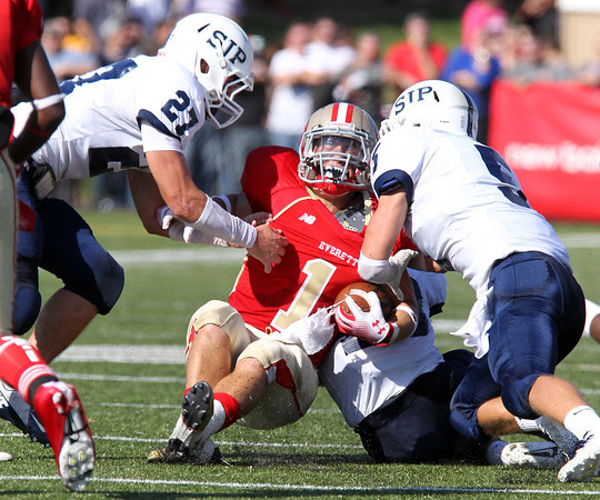 St. John's Prep seniors Alex Moore, left, and Lucas Bavaro, right, bring down Everett ball carrier Kenny Calaj, center, on Saturday afternoon. Top ranked Everett bested the second ranked Prep 19-7. David Le/Staff Photo