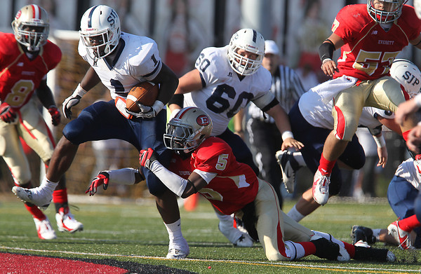 St. John's Prep junior running back Johnny Thomas runs through the tackle of diving Everett junior Lubern Figaro, right, on Saturday afternoon as the top two teams in Massachusetts clashed on the gridiron. David Le/Staff Photo