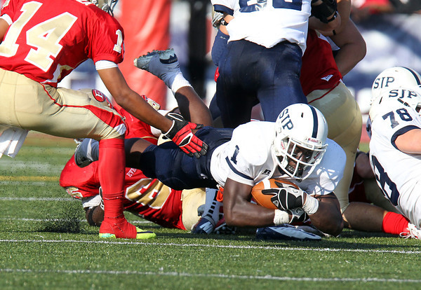 St. John's Prep junior Johnny Thomas dives forward to gain a few extra yards against Everett on Saturday afternoon. Despite Thomas' 19 carries for 101 yards the Eagles fell to the Crimson Tide 19-7 in a battle between the top two teams in Massachusetts. David Le/Staff Photo
