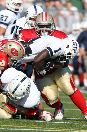 St. John's Prep junior running back Johnny Thomas, center, crashes through a pile of Everett defenders on Saturday afternoon. Thomas ran the ball 19 times for 101 yards, but Everett held off St. John's 19-7. David Le/Staff Photo