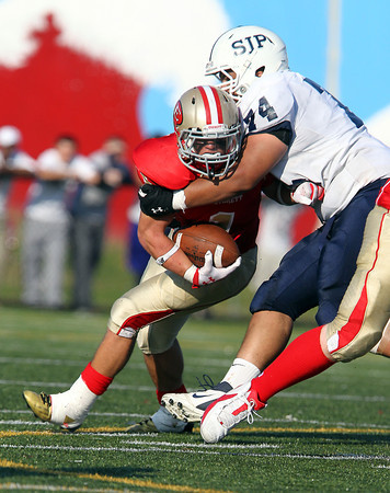St. John's Prep senior Corey Jean-Jacques, right, wraps up Everett ball carrier Kenny Calaj, during the 4th quarter of play on Saturday afternoon at Everett Memorial Stadium. David Le/Staff Photo