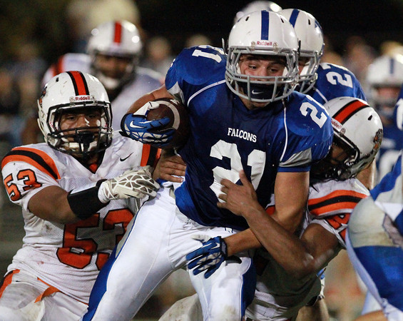 Danvers: Danvers senior running back Alex Valles (21), plows through the tackle of Beverly seniors Sean Winston (53) and Isiah White (22), right, on his way to another big gain on Friday evening. Valles carried the Falcons on his back, rushing for 233 yards and 4 totoal touchdowns, including the go-ahead 47-yard touchdown reception from quarterback Nick Andreas with 3:18 to play. David Le/Salem News