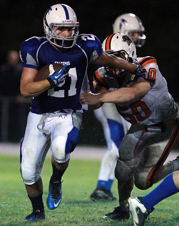 Danvers: Danvers senior running back Alex Valles evades a tackle from Beverly's Zach Duguid and plows forward to pick up a few yards. David Le/Salem News