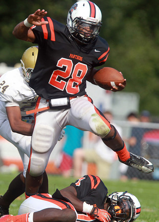 Beverly: Beverly sophomore Matt Madden (28) leaps over fallen teammate Peter Mulumba (7) and rushes forward for a first down against Haverhill on Saturday afternoon. David Le/Salem News