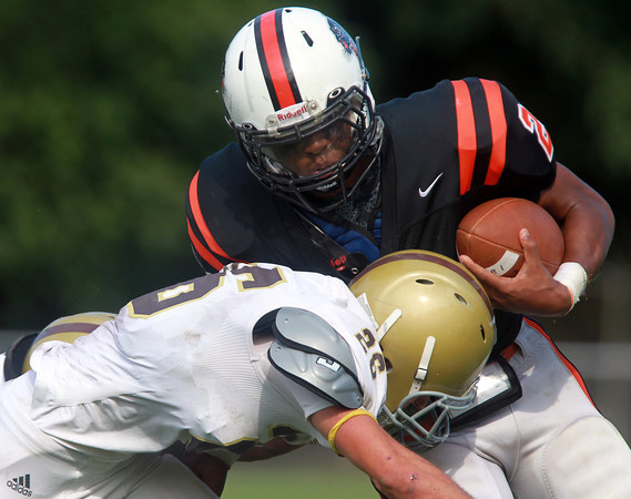Beverly: Beverly sophomore Matt Madden (28) puts his shoulder down and runs over Haverhill senior Josh Dion, left, on a first down run in the third quarter of play on Saturday afternoon. David Le/Salem News