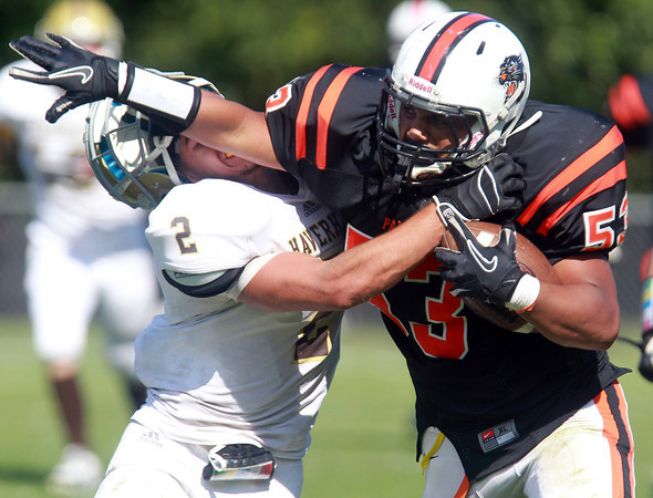 Beverly: Beverly senior middle linebacker Sean Winston (53), right, throws a high stiff arm on Haverhill sophomore Ian Kessel, after intercepting a pass from Hillies quarterback Shane Finn at the end of the first half of play on Saturday afternoon. David Le/Salem News