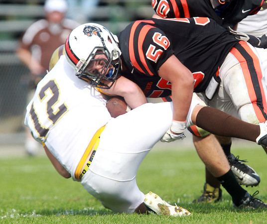 Beverly: Beverly junior Jimmy Kastrinakis (56), right, takes down Haverhill quarterback Shane Finn for a loss during the third quarter of play on Saturday afternoon. David Le/Salem News