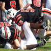 Beverly: Beverly sophomore Matt Madden (28), left, and senior defensive end Zach Duguid (50) take down Haverhill sophomore running back Ian Kessel to force a punt during the third quarter of play. David Le/Salem News