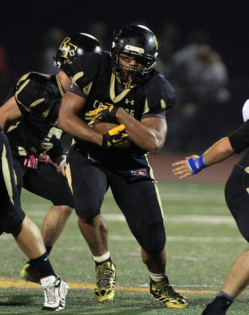 Peabody: Bishop Fenwick's Rufus Rushins blasts through a hole in the North Shore Tech defense on Friday evening. The Crusaders shut out the Bulldogs 41-0. David Le/Salem News