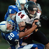 Danvers: Marblehead junior running back Brooks Tyrrell tucks the ball while being brought down by Danvers junior Cris Valles, and junior Joe O'Donnell. David Le/Salem News