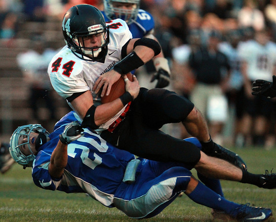 Danvers: Marblehead junior running back Brooks Tyrrell plows over Danvers junior Cris Valles and dives into the end zone for one of his two touchdowns on the evening as the Magicians routed the Falcons 44-0 on Friday evening. David Le/Salem News