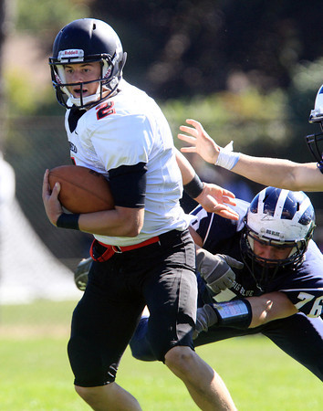 Swampscott: Marblehead senior quarterback Matt Millett (2) shrugs off a tackle from Swampscott junior Ryan Bradley (76) and rushes forward for a big gain. Millett was 16 of 23 for 148 yards and 3 touchdowns in the air, and added 76 yards on the ground to lead the Magicians to a 35-7 win over their Big Blue rivals. David Le/Salem News