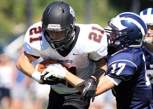 Swampscott: Marblehead senior Trey Blackmer (21) plows forward to pick up a few more yards while being brought down by Swampscott junior Ryan Cresta (17) on Saturday afternoon. David Le/Salem News