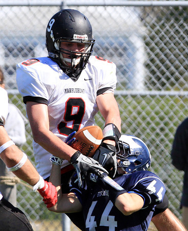 Swampscott: Marblehead junior Will Millett (9) reaches in and strips the ball away from Swampscott senior Michael Faia (44) to break up a would be interception on Saturday afternoon. David Le/Salem News