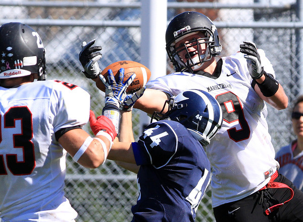 Swampscott: Marblehead junior Will Millett (9) reaches in to knock the ball out of Swampscott senior Michael Faia's hands to break up a potential interception. David Le/Salem News