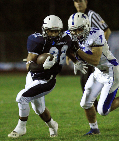 Peabody: Peabody sophomore running back Doug Santos (32) plows upfield while being tackled by Danvers senior linebacker Andy Curtin (40) during the first half of play on Friday evening. David Le/Salem News