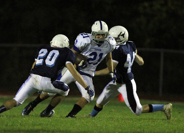 Peabody: Danvers senior running back Alex Valles splits two Peabody defenders on Friday evening. Valles picked up a Tanner fumble and ran it back 85 yards for the game winning touchdown as time expired as the Falcons defeated the Tanners 20-14. David Le/Salem News