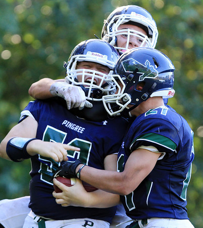 South Hamilton: Pingree sophomore Hunter Jacques (52) is mobbed by teammates Justin Assad (15), and Nikolaus Dreher (27) after he picked off a pass from the Tilton quarterback off a deflection from a teammate and ran it into the end zone for a Highlanders score. David Le/Salem News