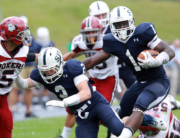 Danvers: St. John's Prep senior running back Johnny Thomas (1), uses a block from teammate Owen Rockett (2), and cuts back upfield against Brockton on Saturday afternoon. Thomas drove the Eagles offense with 272 yards on 31 carries and found the end zone 3 times as well. David Le/Salem News