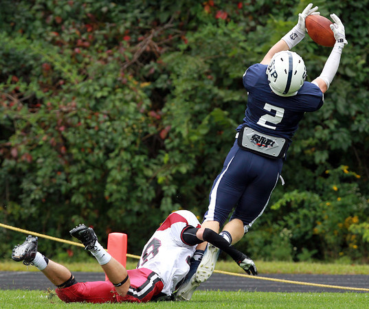 Danvers: St. John's Prep junior wide receiver Owen Rockett tries to reel in a pass from quarterback Michael Geaslen, but can't hold on as Brockton's Walker Smith takes him to the ground. David Le/Salem News