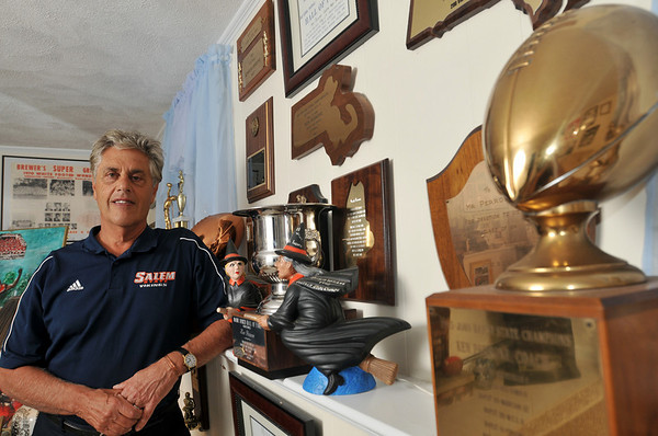 Danvers: Ken Perrone stands next to a wall of his hall of fame plaques.  photo by Mark Teiwes / Salem News