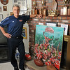 Danvers: Ken Perrone is pictured at his home with some of his many trophies including a painting by David Russell who played tackle on the 1994 Conference Champion and Superbowl team. Photo by Mark Teiwes / Salem News