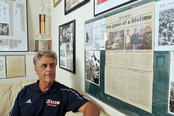 Danvers: Ken Perrone reflects over an old newspaper clipping remembering a game Salem won against Gloucester. Photo by Mark Teiwes / Salem News