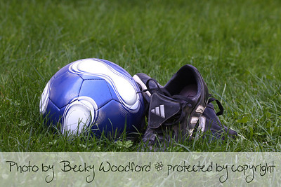 soccer ball and cleats in grass