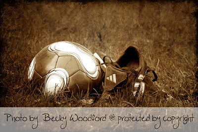 soccer ball in cleats in sepia