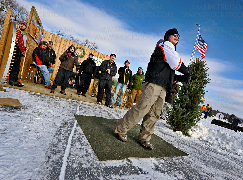 Tony Holm, right, Wayzata, and friends watch his tee shot on the third hole at the Orono Lions 25th annual 'Snowball Open' at Nelson Park held Saturday, Jan. 28, on Long Lake.