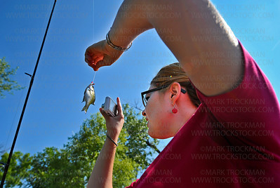 Outgoing Hopkins Raspberry Festival Queen Kariss Mathiason photographs a sunfish she caught off the fishing pier at Shady Oak Lake in Minnetonka Wednesday, July 11, 2012.  Queen Karissa joined dozens of anglers for the Laun E. Anderson Kids Fishing Contest as part of the myriad of activities for young and old celebrating the annual Hopkins Raspberry Festival.