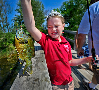 2011-2012 Raspberry Festival Junior Queen Nicolette Stabno, wearing her crown, isn't enthralled by her fishing ability or the big sunfish on the end of her line during the Laun E. Anderson Kids Fishing Contest on Shady Oak Lake in Minnetonka Wednesday, July 11, 2012.