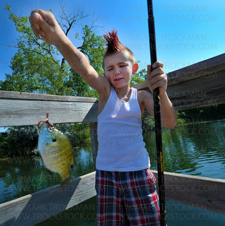 "Eight-year-old Anthony ""A.O."" Olson waits for his mom to unhook a sunfish he caught off the fishing pier at Shady Oak Lake in Minnetonka Wednesday, July 11, 2012.  Anthony joined dozens of young anglers for the Laun E. Anderson Kids Fishing Contest as part of the myriad of activities for young and old celebrating the annual Hopkins Raspberry Festival.  A.O. was the 2010-2011 Raspberry Festival Junior Prince."