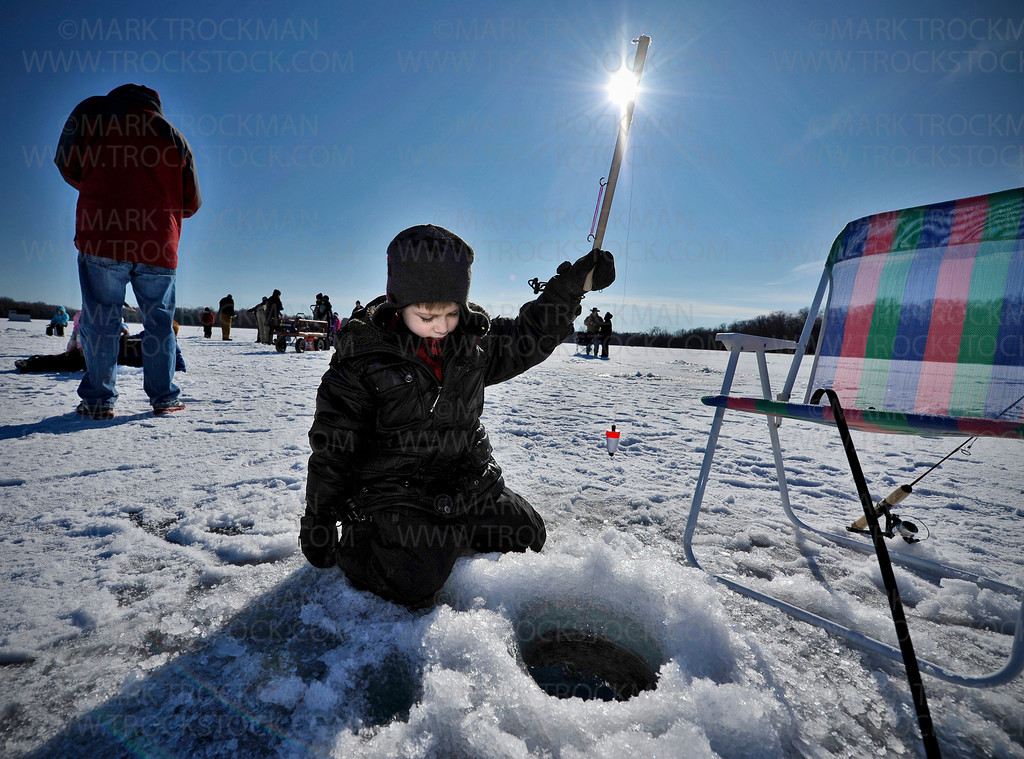 Four year old Parker Wallin, Cottagewood, conjures up a newly learned jigging technique through a hole dug on Lake Auburn in the Lowry Nature Center in Carver Park Reserve Saturday, Feb. 18, in Victoria.  Parker and his Grampa Don Peterson, left, attended 'Take a Kid Ice Fishing' to teach Parker proper ice fishing techniques and how to make his own jigging pole.