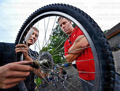 First-time Tour de Tonka rider Ryan Madera, right, Shorewood, gets a broken spoke fixed by Maple Grove Cycling store manager Travis Dorweiler in Excelsior Commons Park, the first big rest stop on the multiple-length, annual bicycle ride Saturday, August 4, on the shore of Lake Minnetonka.