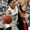 Missouri Southern's Reggie Tharp (0) dishes off to a teammate as Pittsburg State's Grant Lozoya defends during their game on Tuesday night at Leggett & Platt.<br /> Globe | Laurie Sisk