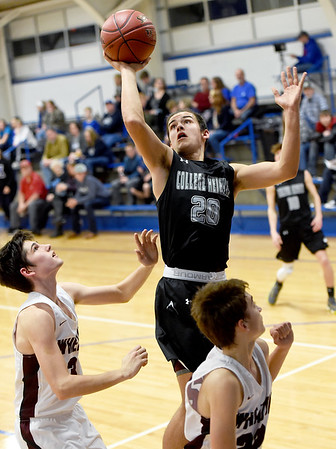 College Heights senior Clay Sitton (20) puts up a shot as Wheaton's Ty Hudson, left and Kelton Park look on during their game in the Warrior Classic on Friday night at McAuley High School.<br /> Globe | Laurie Sisk