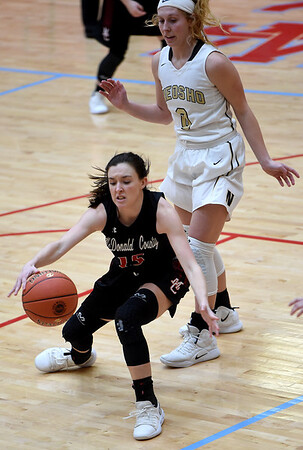 McDonald County's Ragan Wilson tracks down a loose ball as Neosho's Madison Flynn (0) looks on during their Class 4 District 12 game on Saturday at Webb City High School.<br /> Globe | Laurie Sisk