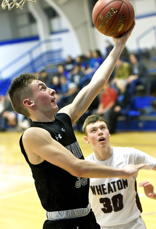 College Heights senior Skyler Levendosky (35) gets past Wheaton's Zac Leverich (30) during their game in the Warrior Classic on Friday night at McAuley High School.<br /> Globe | Laurie Sisk