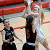 Neosho's Madison Flynn shoots over McDonald County's Sydney Killion (5) as Lily Allman (10) looks on during their Class 4 District 12 game on Saturday at Webb City High School.<br /> Globe | Laurie Sisk