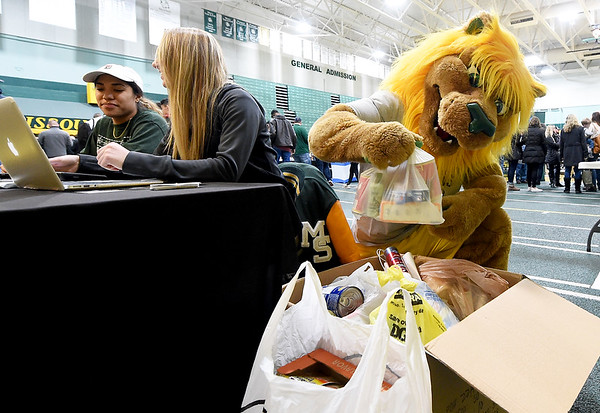 """Missouri Southern mascot """"Roary"""" the Lion checks out donations to the Lion Co-op food pantry on Tuesday night at Leggett & Platt. Volunteers Samantha Pollard, left and Sydney Dose work the donation table during the MSSU basketball games against Pittsburg State. <br /> Globe 