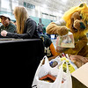 "Missouri Southern mascot ""Roary"" the Lion checks out donations to the Lion Co-op food pantry on Tuesday night at Leggett & Platt. Volunteers Samantha Pollard, left and Sydney Dose work the donation table during the MSSU basketball games against Pittsburg State. <br /> Globe 