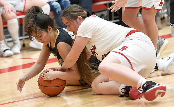 From the left: Neosho's Melia Robertson and Carl Junction's Ashley Stokes battle for a loose ball during their semifinal game of the Class 4 District 12 tournament on Wednesday night at Webb City High School.<br /> Globe | Laurie Sisk