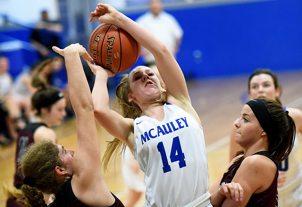 McAuley's Courtney Bates (14) drives between Wheaton's Zoie Simpson, left and Tori Goostree during their championship game of the Warrior Classic on Saturday at McAuley High School.<br /> Globe | Laurie Sisk