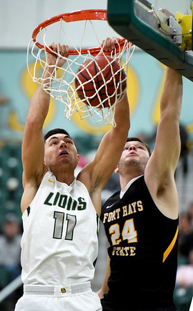 Missouri Southern's Kinzer Lambert (11) dunks an Elyjah Clark assist as Fort Hays State's Payton Stephens (24) defends during their game on Saturday at Leggett & Platt.<br /> Globe | Laurie Sisk