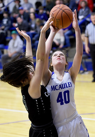 McAuley's Becca Frietas (40) drives to the basket as College Heights' Lainey Lett (25) defends during their game on Friday night at McAuley.<br /> Globe | Laurie Sisk