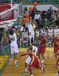 Here is an alley oop pass to Anthony Jones and you can see the track of the ball as it comes down to him at the rim of the basket. He almost flew too far behind the back-board to complete the shot, but he barely tipped it in for the score.