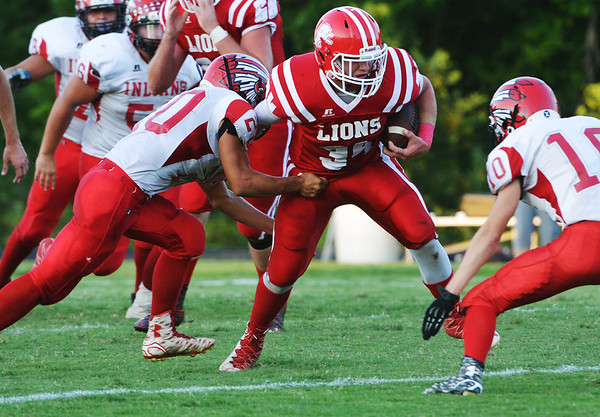 Globe/Roger Nomer<br /> Baxter Springs' Doug Dardenne runs under pressure from Oswego's Bryan Siu (20) and Ethan Garris (10) during Friday's game in Baxter Springs.