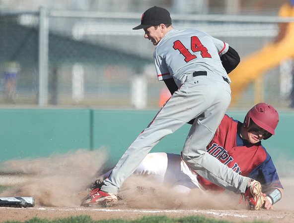 Joplin's Tristan Ash slides safely into home after reaching base on a two-rbi triple during a big fifth inning for the Eagles. Defending on the play is Branson's Lachlan Maher. <br /> Globe | Laurie Sisk
