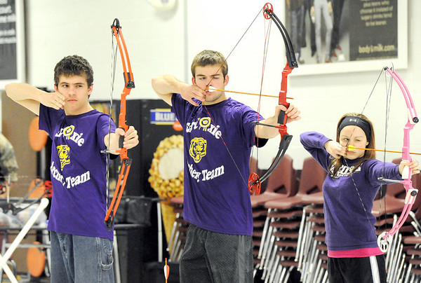 From the left: Sarcoxie archers Chris Lingenfelter, Brice Dobbs and Alyssa Lambeth hone their skills on Wednesday during archery team practice at Sarcoxie High School.<br /> Globe | Laurie Sisk